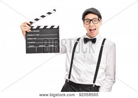 Young movie director holding a movie clapperboard and leaning against a wall isolated on white background