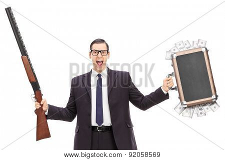 Angry businessman holding a rifle and a bag full of money isolated on white background