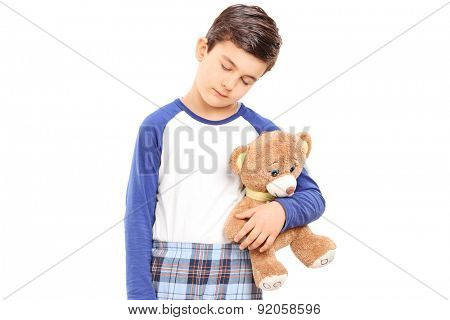 Sleepy boy holding a teddy bear isolated on white background