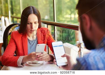 concept photo of smartphone addiction. young woman and man sitting in cafe with smartphone and do not looking at each other
