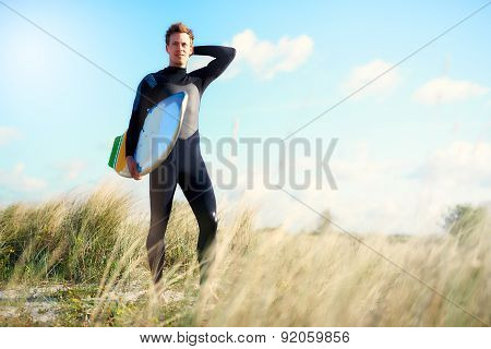 Surfer Posing With His Board Under His Arm