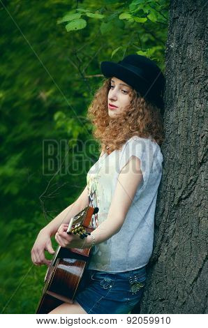 Young Girl With Guitar Leaning On A Tree