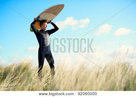 Strong Young Surfer Crossing A Sand-dune