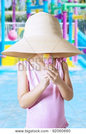 Child With Hat Eating Ice Cream At Pool