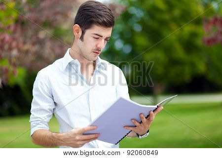 Male student reading outdoor