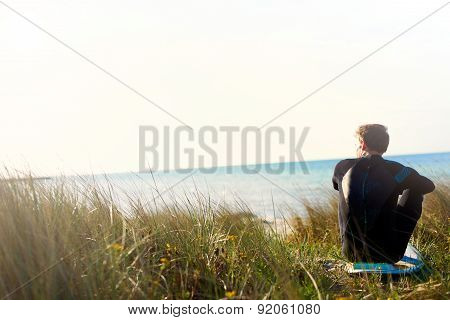 Surfer Sitting On His Board Overlooking The Ocean