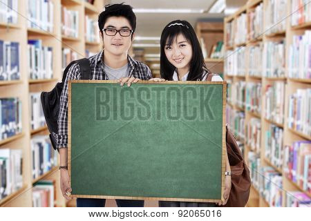 Students Holds Billboard In Library