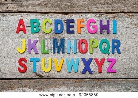 Colorful wooden English alphabet set on grunge wooden background.