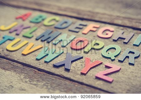 Colorful wooden English alphabet set on grunge wooden background, focus on alphabet X.