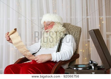 Santa Claus sitting with list of children wishes in comfortable chair near fireplace at home