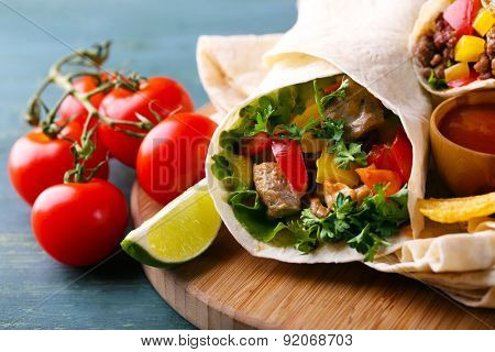 Homemade tasty burrito with vegetables, potato chips on cutting board, on wooden background