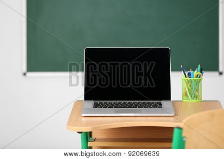 Wooden desk with stationery and laptop in class on blackboard background