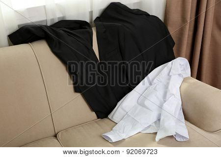 Messy school clothes for boy on sofa