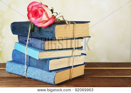 Tied books with pink rose on wooden table, closeup