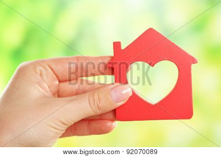 Female hand holding model of house on bright background