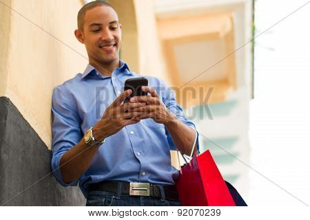 African American Man Text Messaging On Phone With Shopping Bags
