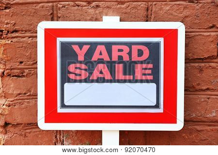 Wooden Yard Sale sign on red brick wall background