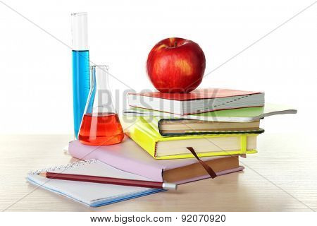Desk with books and test tubes isolated on white