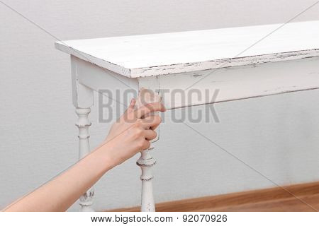 Female hand removing paint from wooden table for decoration, indoors