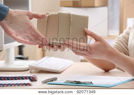 Woman gives parcel in post office