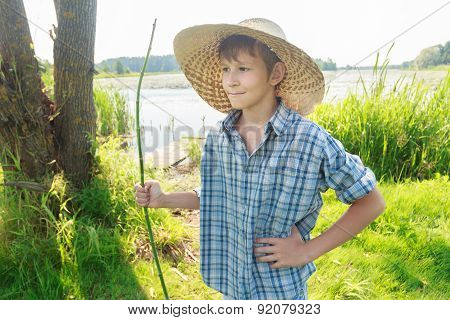 Three-quarter View Portrait Of Standing Angler Teenage Boy Wearing Plaid Shirt And Straw Hat