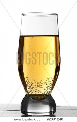 Glass of water with bubbles on table isolated on white