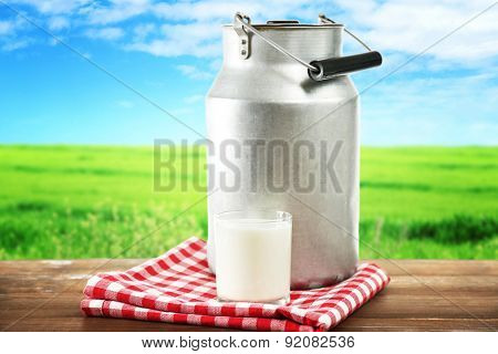 Retro can for milk and glass of milk on wooden table, on white background