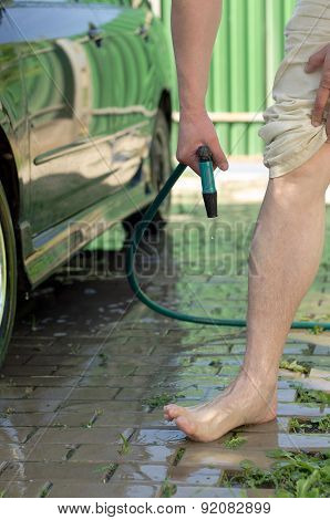 Men's feet are watered from hose with cold water