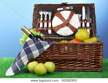 Tasty sandwiches on wicker picnic basket on blue background