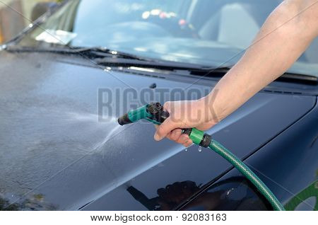 Man's hand washing a car with a hose