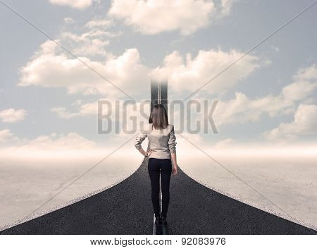 Business woman looking at road that goes up in the sky concept