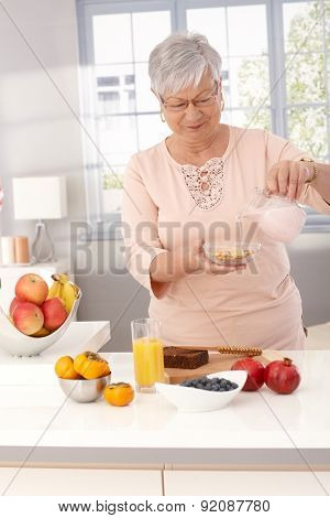 Mature woman making breakfast cereal and healthy food.