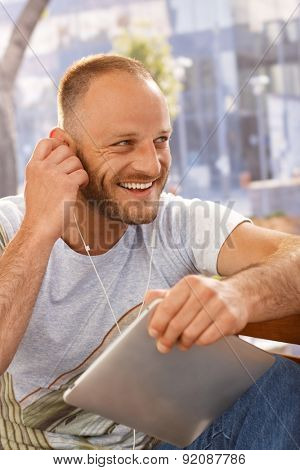 Handsome young man sitting outdoors, using earbuds and tablet computer, looking away.