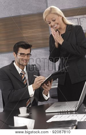 Businesswoman happy as partner signing contract, rubbing hands excited.
