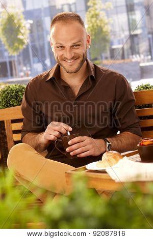 Handsome man sitting outdoors, having coffee, smiling happy, looking at camera.