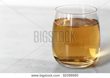 Glass of water with bubbles on table close up