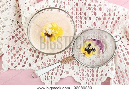 Candied sugared violet flowers, glass bowl with sugar,sieve on wooden background