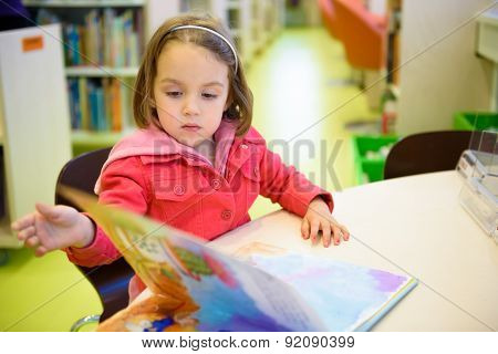 Little Girl Is Browsing A Book In The Library