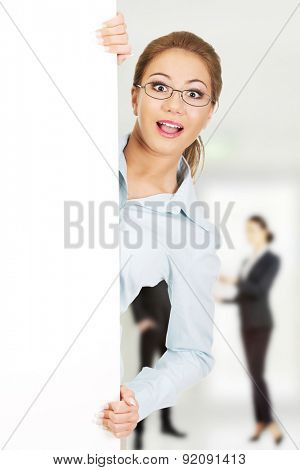 Beautiful shocked business woman presenting your product.