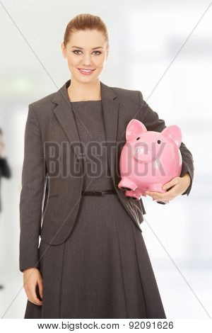 Business woman saving money in piggybank.