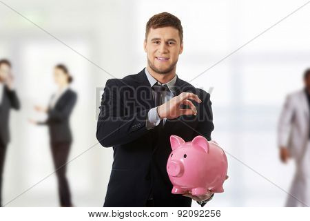 Young businessman putting a coin to piggybank.