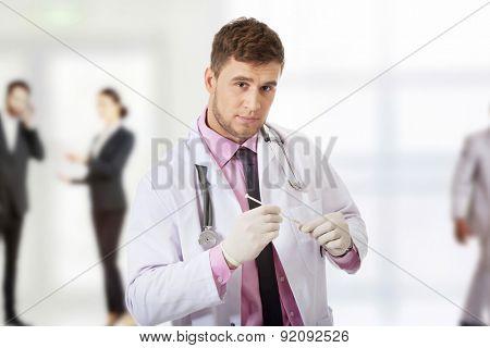 Handsome male dentist doctor holding a syringe.