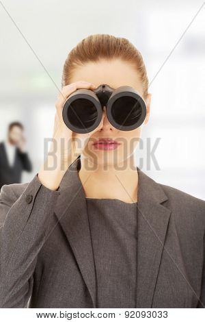 Caucasian businesswoman looking through binoculars.