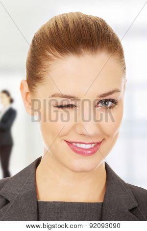 Beautiful businesswoman blinks her eye.