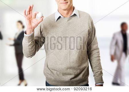 Mature man holding golf ball.