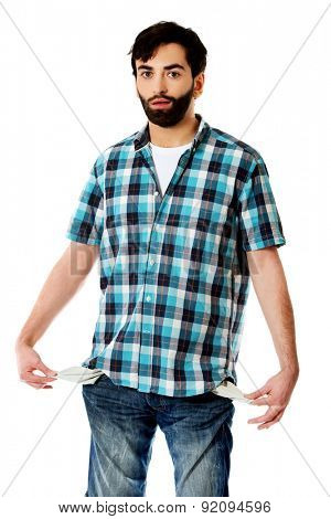 Broke young man showing his empty pockets.