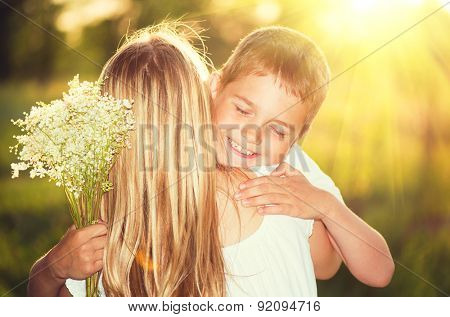 Mother and her little son with bouquet of flowers outdoors, Happy family mom and kid kissing and hugging. Mother's day gift.