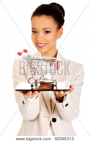 African businesswoman with shopping cart and tablet.