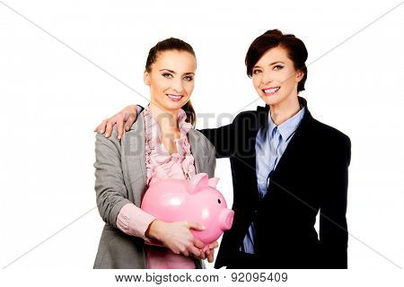Happy two businesswoman holding a piggybank.
