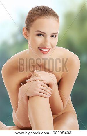 Beautiful spa topless woman sitting.